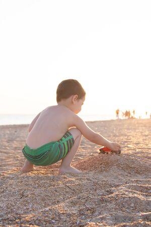 一个男孩在海滩上玩打字机。儿童游戏。海滩在夏天。小孩子 。沙滩
