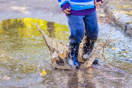 A little boy is jumping in a puddle. A boy in rubber boots. Happy childhood. Puddles after the rain. Warm summer evening. Kids games