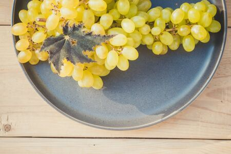 Branch of green grape raisins on a plate. Fruit on a plate. Green berries. Plate on wooden background