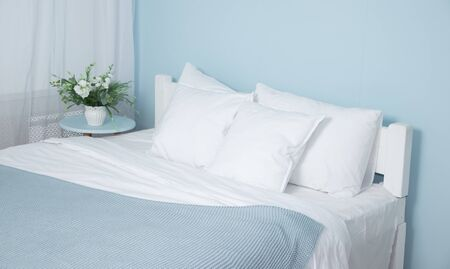 Double bed with lifting mechanism and mattress. The white mattress. Large bright bed. The bedspread is blue