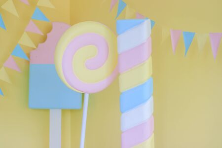 Children's holiday decoration. Holiday decoration. Sweet decorations on yellow background. Big sweets are decorative in the Studio. Children's holiday