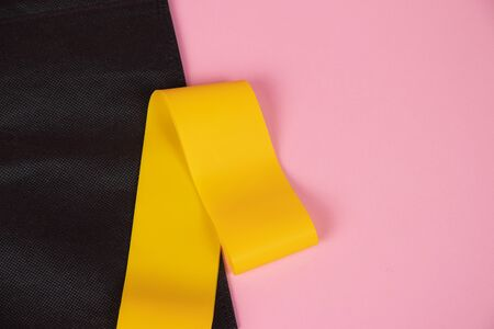 Sports yellow elastic band . Sports equipment, sports at home, equipment for home sports. Yellow rubber band on a pink background. Sport