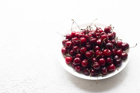 Cherry berry on a white plate . Summer berry. Berries on a plate on a white background. Article about berries. The berry season.