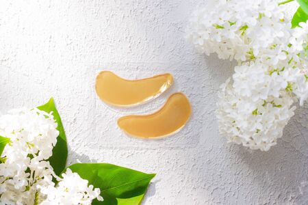 Hydrogel yellow patches under the eyes and flowers. Lilac flowers. Light background. Space for the text. beauty industry. Skin care. Patches under the eyes Copy spase