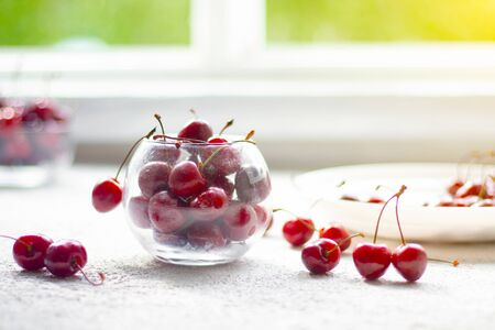 Cherry berry in a vase. Cherry berry in a transparent plate on a light background . Summer red berries.