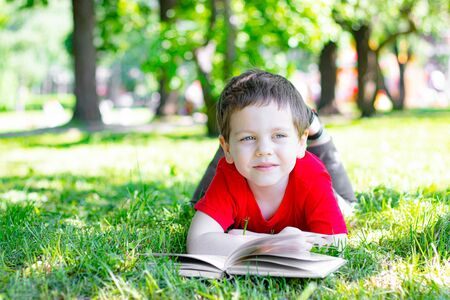 The boy is lying on the grass with a book. The boy is lying on the grass and reading a book . Young child. Happy childhood . Hobbies and recreation. Reading in nature. Article about childrens books. Article about fairy tales for children.