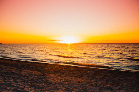 Sunset at sea. Warm sunny sunset over the sea. Sea waves. The sun sets over the horizon. The Gulf of Finland