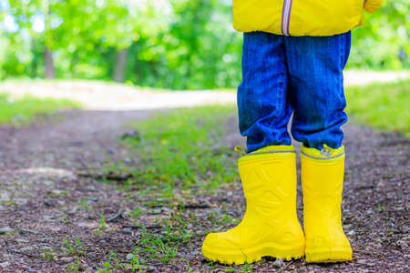 Yellow rubber boots on the child's feet . Shoes for wet weather. Children's shoes. Ads for rubber boots. Children's feet are on the path in the Park
