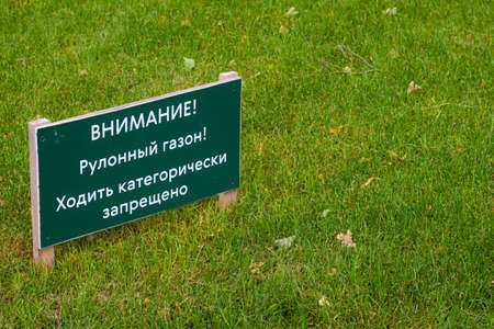 Sign on the lawn it is forbidden to walk on the lawn . Prohibition to walk on the lawn. Rolled lawn. Green grass