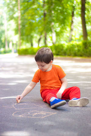 A boy draws with crayons on the asphalt . Painting. Summer. Summer games on the street. Childrens entertainment and leisure. Chalk for asphalt . 版權商用圖片