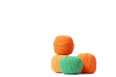 Colored balls of crochet thread on a white background . Copy space. The tangles are arranged in a column. Article about crocheting. Selection of threads for crocheting. Features of choosing a material for knitting. Made by the hands. Leisure for pensioners.