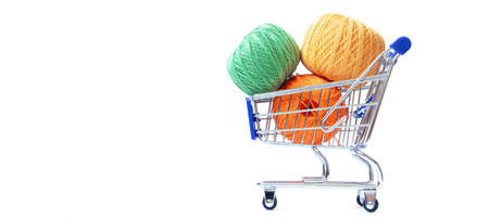 Trolley with yarn for knitting. Yarn for crocheting. Design of the embroidery section. Needlework. Hobbies and recreation. Colored threads on a white background. Copy space