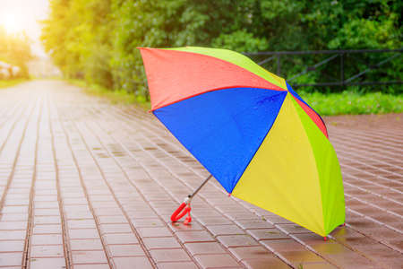 An open colored umbrella stands on the asphalt. Summer rain. Article about choosing an umbrella. Childrens bright umbrella. . Copy space 版權商用圖片