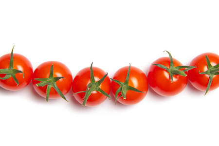 Cherry tomatoes on a white background . Tomatoes in the line. Isolated background. Vegetables. Vegetarianism. Article about tomatoes. Article about vegetables. Copy space 版權商用圖片