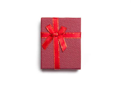 Red gift with a bow on a white background . Red bow. Bow on the gift. Gift wrapping. isolated background. Copy space. Article about gifts. New year and Christmas. Valentines day.