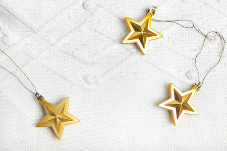 Christmas toys stars are Golden . Golden Christmas toys. White knitted fabric. New year and Christmas holidays. Christmas layout on top. Article about the holiday.