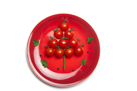 tomatoes in the form of a Christmas tree . cherry tomatoes on a red plate. Christmas and new year. Christmas layout. copyspace. Isolate. Food and food products. Article about cooking for the new year.
