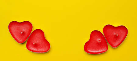 Candles in the form of hearts on a yellow background. Red candles. Red hearts. Yellow background. Copy space. Valentine's Day. Holiday. An article about celebrating Valentine's Day .. An article about love.