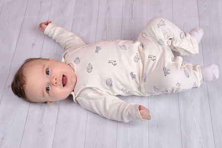 Cute baby boy supine and smiling on bright wooden floor. Фото со стока