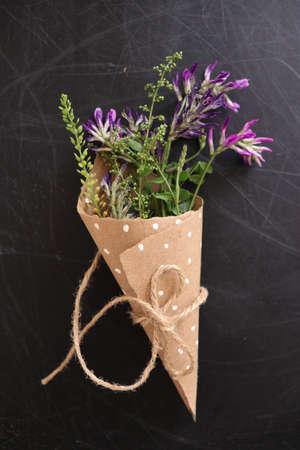 Bouquet of purple flowers in a craft bag. Flower design on chalk Board