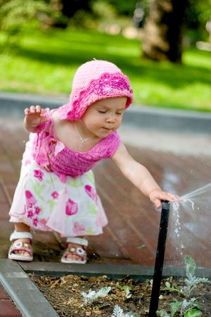 A pretty kid girl playing with sprinkler Stock Photo - 1907742