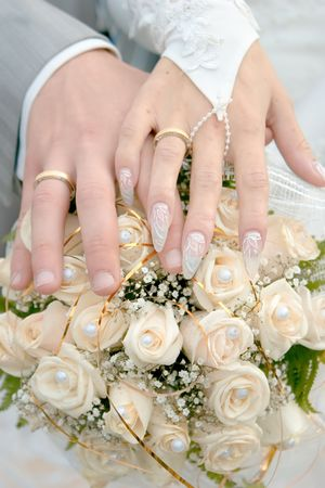 Wedding rings and hands under bridal bouquet from white roses and pearls Stock Photo - 2034656