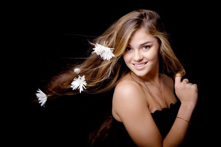 Beautiful attractive young  smiling girl with white flowers in her hair blowed by wind on black