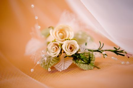 buttonhole: Wedding floral buttonhole with pearls on beige background and veil Stock Photo
