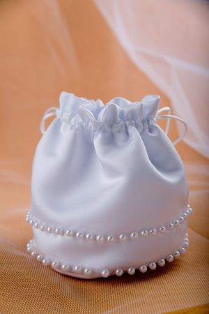 Bridal white silky handbag with pearls and veil on beige background photo