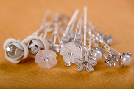 Group of silver wedding pins on beige background photo