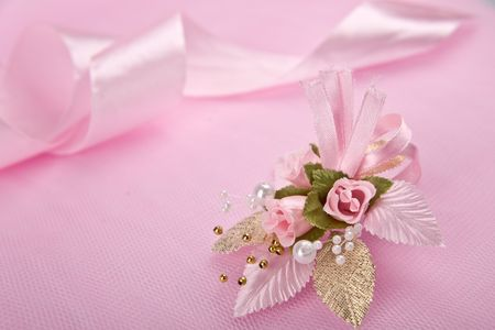 satin ribbon: Wedding floral buttonhole with pearls on pink background and satin ribbon behind
