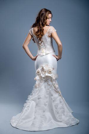 Slim beautiful woman with long hair wearing luxurious wedding dress over gray studio background Stock Photo