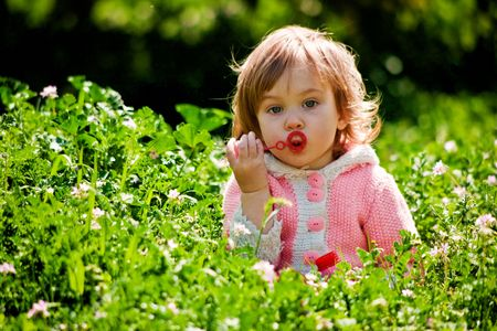 sud: Child sitting at green grass among flowers and blowing soap bubbles in spring