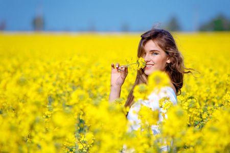 Nice girl holding flower in rape field photo