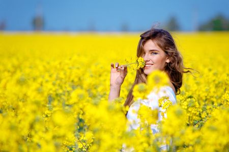 Nice girl holding flower in rape field Stock Photo - 2941110