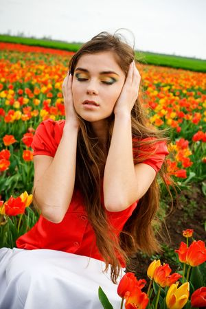 Beautiful woman with long hair in tulips field photo