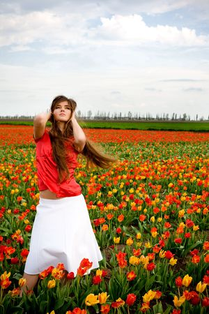 Beautiful young model in tulips field photo