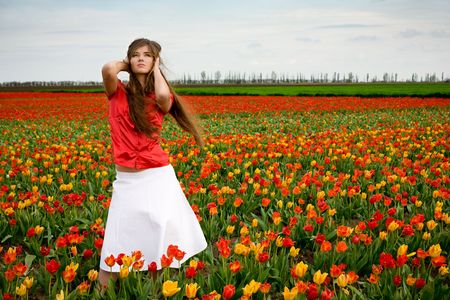 Young nice girl standing in red and orange tulips field Stock Photo - 2941133