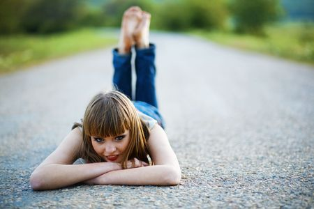 Young woman lying down on road and looking at camera Stock Photo