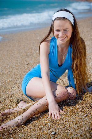 Beuatiful girl in blue dress sitting on sand at beach and smiling photo