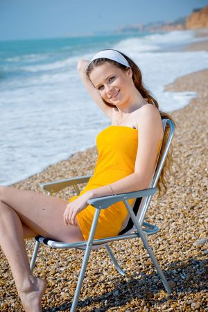 Young beautiful girl posing and smiling in chaiselongue at sea coast Stock Photo - 3041558