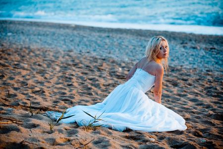 Trash the wedding dress series. Bride sitting on sand at beach during sunset. photo