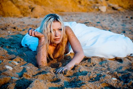 trash the dress: Trash the wedding dress series. Bride lying on sand and looking at camera, she looks tired.