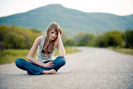 barefoot teens: Tired young girl sitting down on road