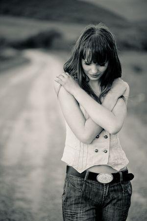 occhi tristi: Stanco adolescente ragazza soggiornare su strada, l'immagine in color seppia Archivio Fotografico