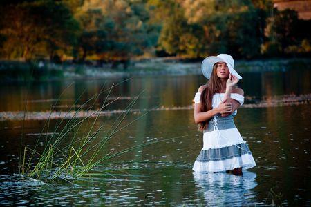 Beautiful woman in hat posing in lake water photo