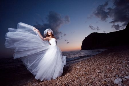 Bride posing showing her wedding dress on sunset beach photo