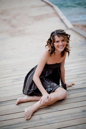 Nice smiling girl sitting on wooden berth near sea photo