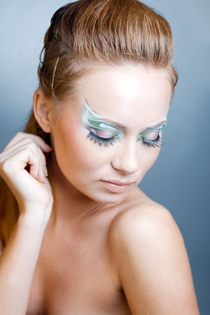 Fashion model with ceremonial make-up and face-art on blue studio background Stock Photo - 3765923