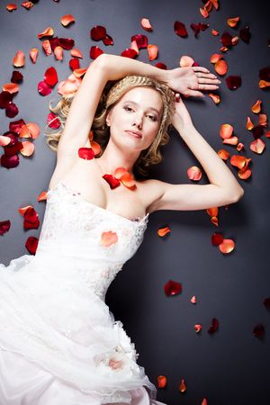 Beautiful sexy bride lying on the floor among red rose petals on gray background photo